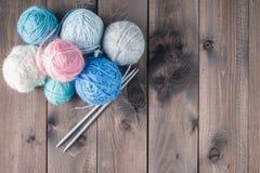 编织的五颜六色的毛线在一张棕色木桌上 免版税库存照片