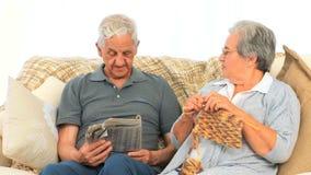 编织的妇女,当她的丈夫读报纸时 股票录像