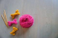 编织的桃红色在棕色木背景的毛线和钩针编织 免版税图库摄影
