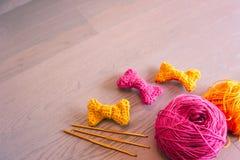 编织的桃红色在棕色木背景的毛线和钩针编织 免版税库存照片