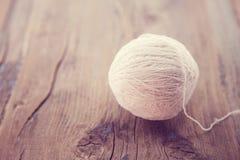 编织的白色毛线在一张土气木桌上 库存图片