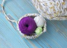 编织的,在木土气背景的钩针编织白色,绿色和紫罗兰色小棉纱品球 混合物毛线球 免版税库存图片