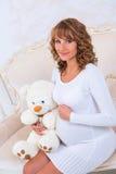 编织礼服的特写镜头怀孕的女孩有玩具熊的 免版税库存照片