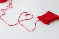 编织针和螺纹在心脏形状 库存照片