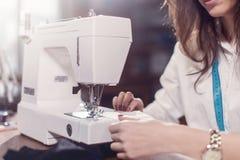 缝与缝纫机的女性裁缝的播种的图象美好的鞋带坐在女装裁制业演播室 免版税库存照片