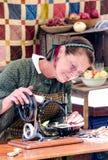缝合与一个古色古香的机器的妇女 库存照片