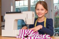 缝合与一台缝纫机的女孩一块桃红色和白色镶边布料 图库摄影