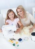 缝合与她的母亲的美丽的女孩 免版税图库摄影