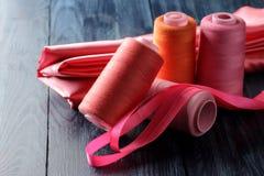 缝合和针线螺纹和织品剪刀的辅助部件在蓝色木背景 免版税库存图片