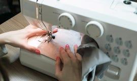 缝合在一个缝纫机特写镜头的妇女轻的织品 侧视图 库存照片