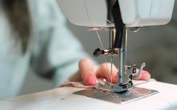 缝合在一个缝纫机特写镜头的妇女轻的织品 图库摄影