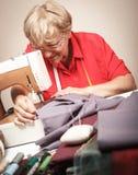 缝合在一台缝纫机的资深妇女 库存照片