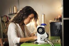 缝合在她的车间的美丽的裁缝 免版税库存照片