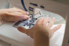 缝合在缝纫机的接近的妇女手 免版税库存照片