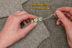 缝合在钩针编织的灰色织品上的手按钮 免版税库存图片