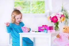 缝合她的玩偶的小女孩一件礼服 库存照片