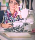 缝合的少妇,当坐在她的工作地点时 免版税库存图片