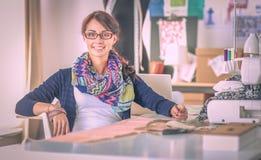 缝合的少妇,当坐在她的工作地点时 库存照片