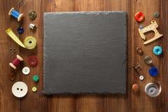 缝合的工具和辅助部件在木头 免版税库存照片