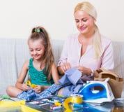 缝合的母亲教的女儿 免版税库存图片