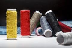 缝合的缝制的螺纹,彩虹颜色 在与地方的黑背景您自己的文本的 免版税图库摄影