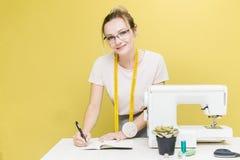 缝合的车间 拿着评定裁缝工作的现有量 一位年轻裁缝的画象有笔记本的在色的背景 免版税库存图片