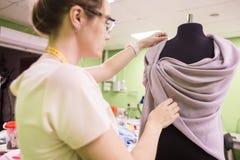 缝合的车间 拿着评定裁缝工作的现有量 工作在礼服的年轻裁缝在演播室 库存图片