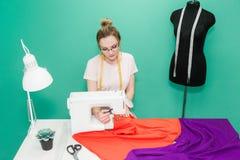 缝合的车间 拿着评定裁缝工作的现有量 年轻女人与在色的背景的缝纫机一起使用 免版税库存照片