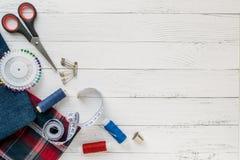 缝合的辅助部件、牛仔裤和格子花呢披肩织品在白色木背景 织品,缝合针线,针,别针,剪刀,按钮 免版税库存图片