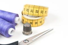 缝合的辅助部件和工具、中等紫色缝合针线、黄色测量的磁带有黑数字的,剪刀和金属顶针o 免版税库存图片