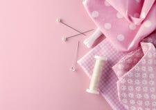 缝合的集合:织品、螺纹和别针在桃红色 免版税库存图片