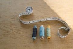 缝合的静物画-不同的颜色棉花螺纹短管轴,顶针,针,测量的磁带 图库摄影