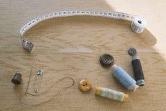 缝合的静物画-多彩多姿的棉花螺纹短管轴,顶针,针,测量的磁带 免版税图库摄影