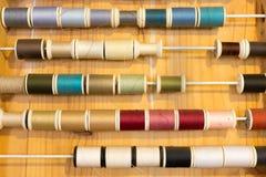 缝合的颜色行穿线在木桌上的框架 免版税图库摄影
