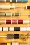 缝合的颜色行穿线在木桌上的框架 免版税库存图片