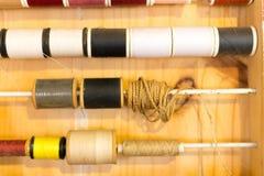 缝合的颜色行穿线在木桌上的框架 免版税库存照片