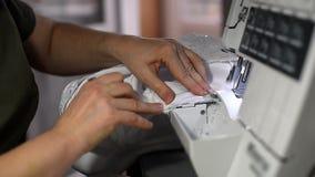 缝在overlock机器的女性播种的手白色婚纱工作 做边缘加强纺织品边缘 影视素材