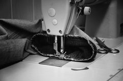 缝纫机和牛仔裤在缝合的车间 单色 免版税库存图片