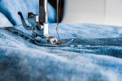 缝纫机和蓝色牛仔裤织品 库存照片