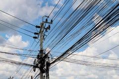 缠结在路,在泰国电能的导线的导线在走的街道旁边天空背景 库存照片