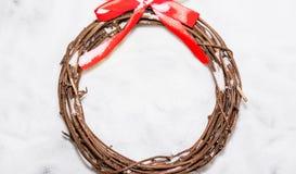 缠绕编织从与桃红色丝带的分支,在白色雪 免版税库存图片