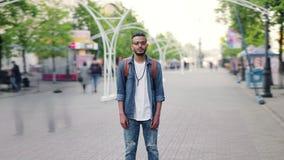 缩小年轻人阿拉伯身分时间间隔在拥挤的街的有背包的 股票视频
