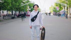 缩小站立户外在有委员会的街道的年轻溜冰板者时间间隔 影视素材
