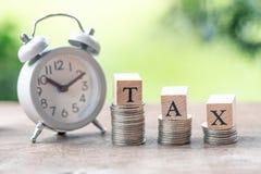 缴纳年收入税年 木词在堆安置的税硬币使用作为背景企业概念和财务 库存图片