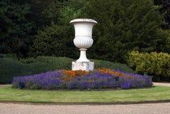 缸和花床在公园或庭院 免版税库存图片