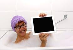 浴缸的热心成熟妇女有片剂计算机的 免版税库存图片