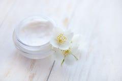 罐与茉莉花花的秀丽奶油在白色木桌上 关闭 免版税图库摄影