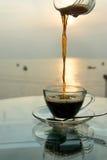 从水罐倾吐的无奶咖啡入玻璃 库存照片
