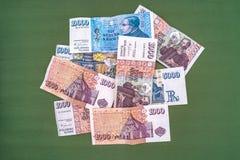 罐冰岛放置在绿色地毯的克朗钞票作为bac 免版税库存照片