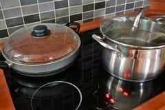 罐和平底锅在厨房归纳火炉 图库摄影